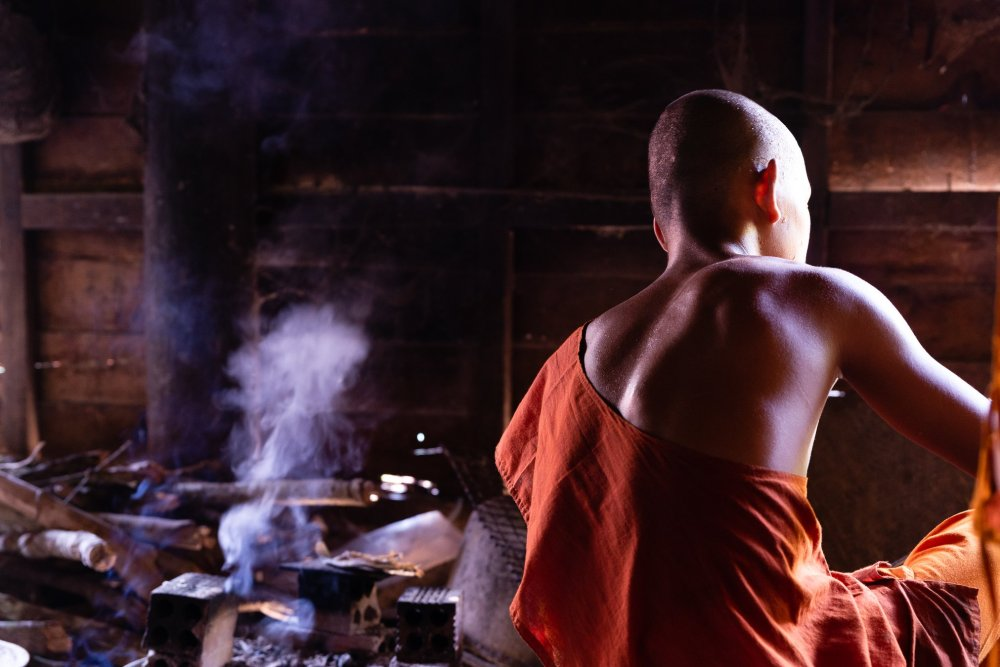 Photo of a monk with the smoke in the background as he prepares their daily meal