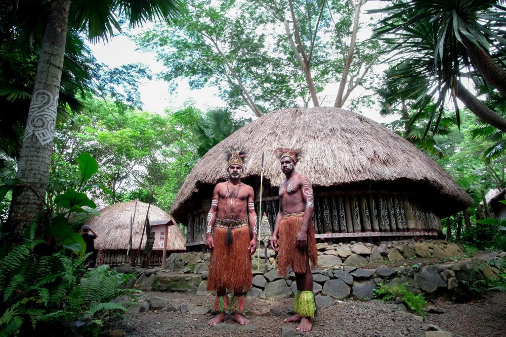 Photo of two tribesmen standing in front of their home/hut