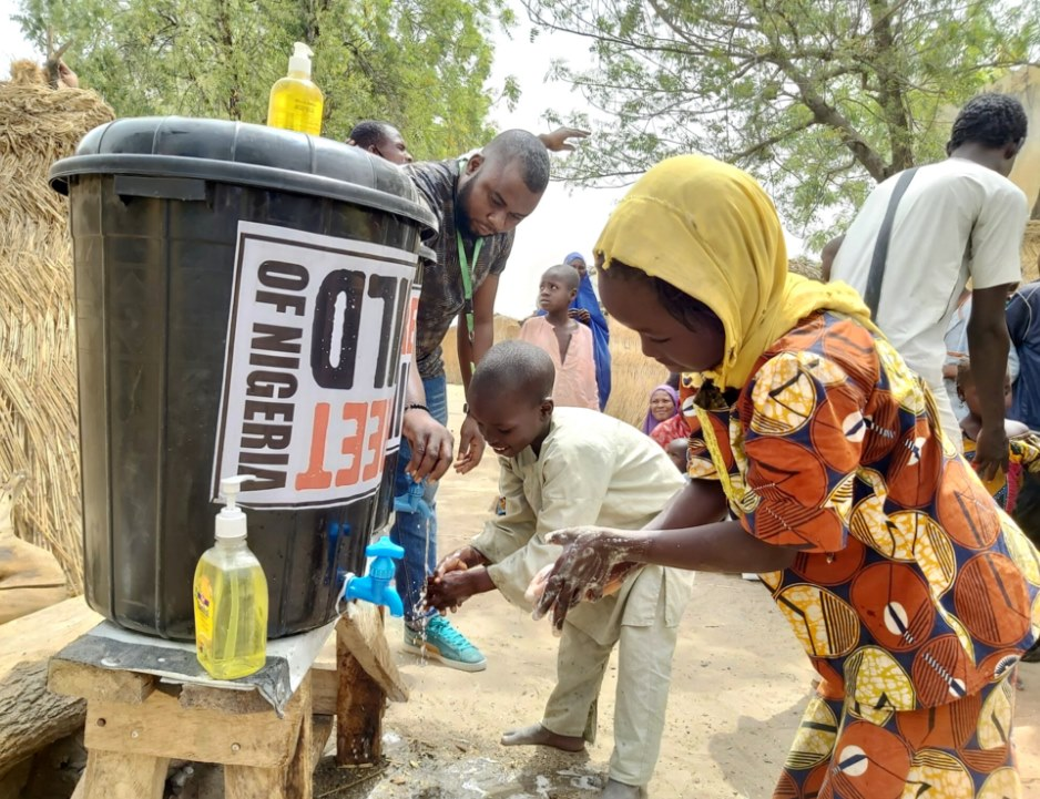 Two kids making use of Street Childs hand washing station
