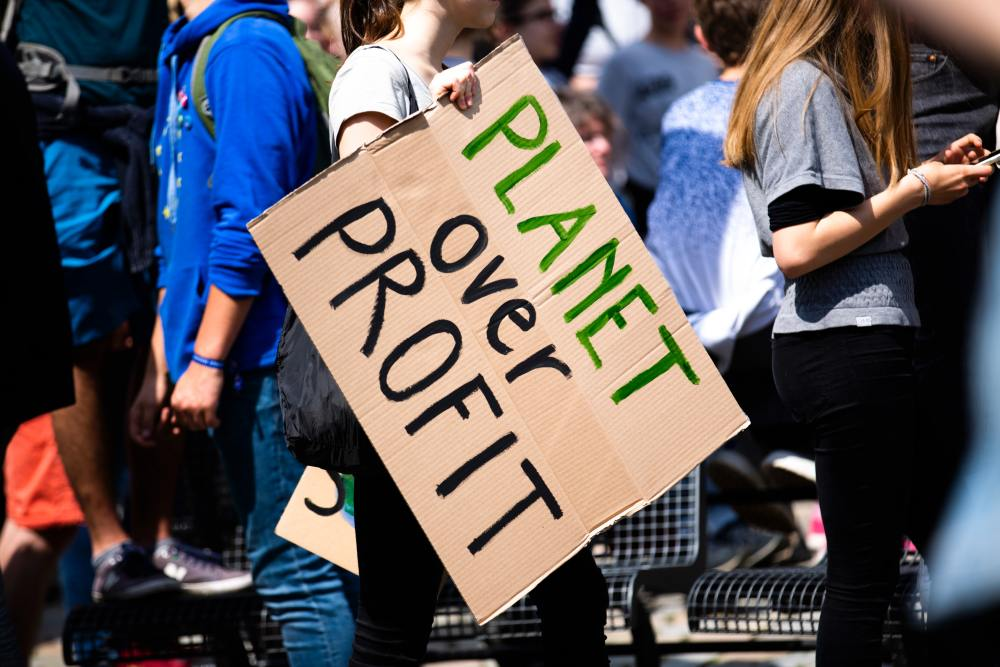 A girl holding up a cardboard square that says Planet over Profit