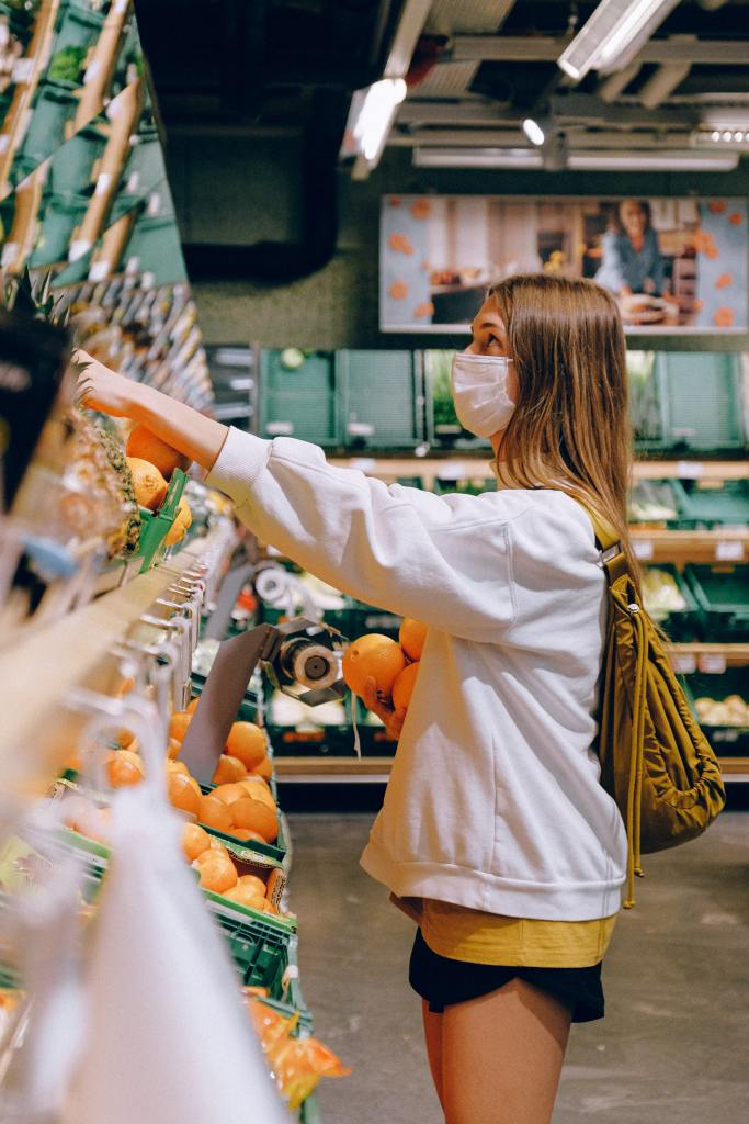 Photo of a woman wearing a face mask shopping for fruit - a now common image since COVID-19