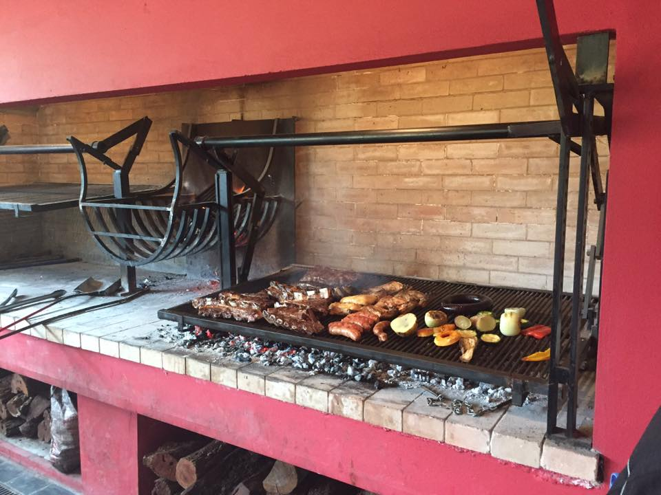 Photo of a grill with meat and veg on it