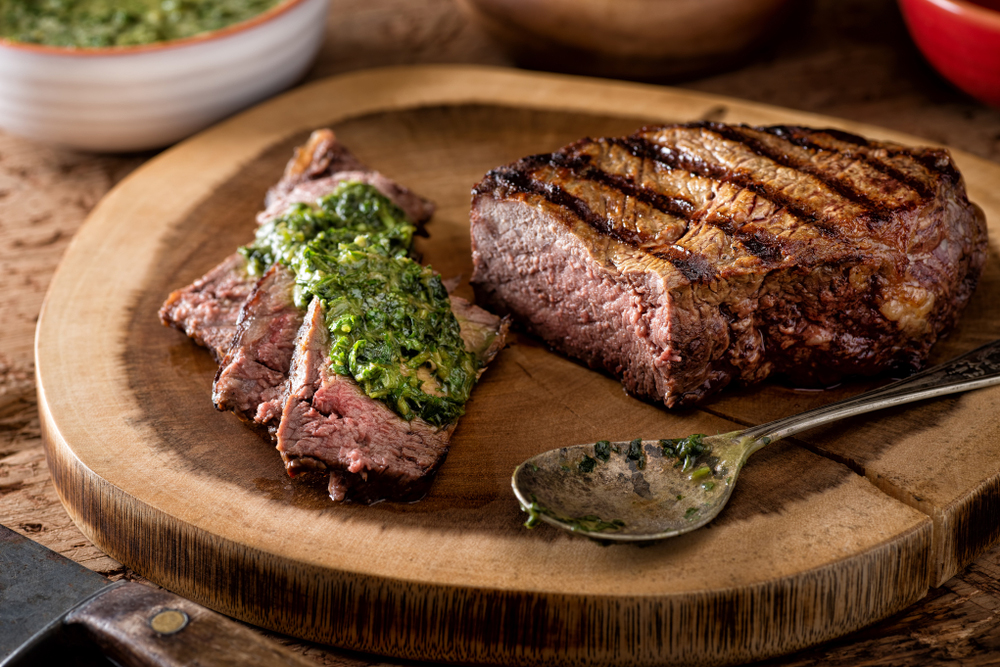 Photo of a large piece of beef with chimichurri sauce on it