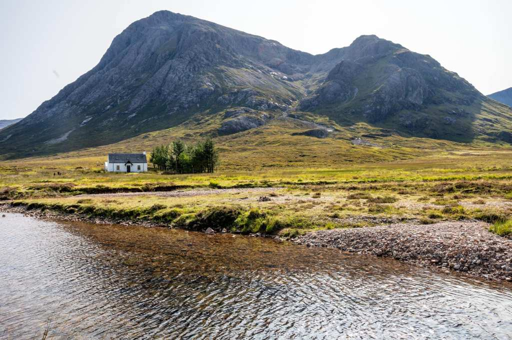 Photo of a small white hut in front of a formidable mountain in Scotland