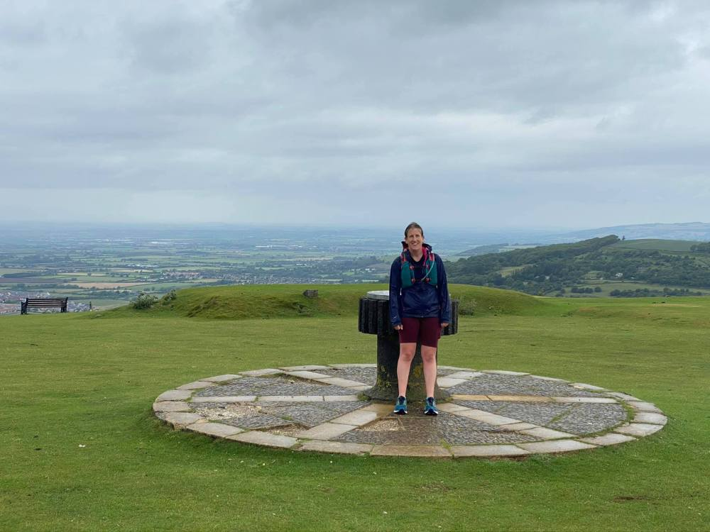 Rachel standing in front of the cairn that marks the top of Cleeve Hill - the end of our first leg of the Cotswold Way
