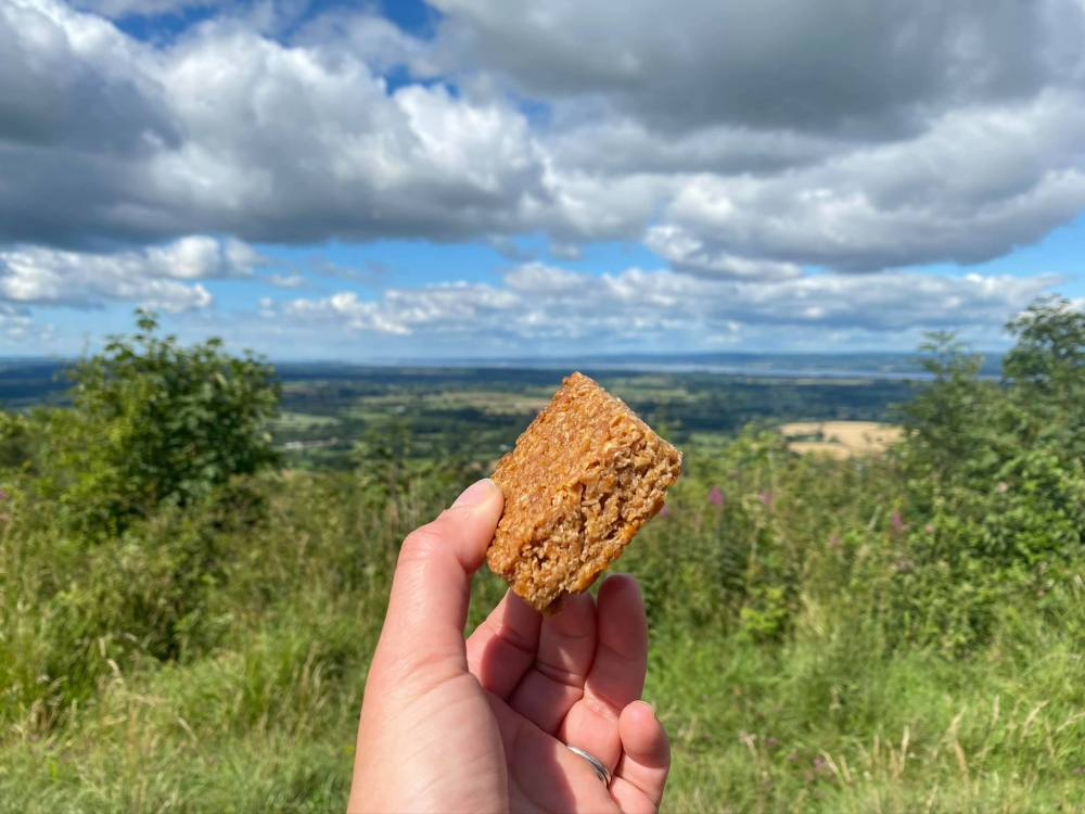 A photo of my hand holding a flapjack with the Severn Estuary in the distance.