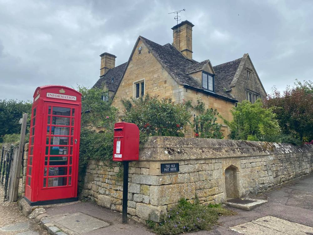 A typical Cotswold stone cottage with a red telephone box and letter box next door. Quintessential English