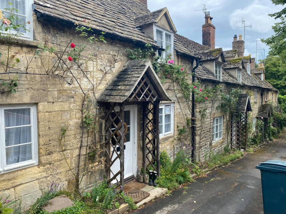 A row of terraced Cotswold stone cottages in the village of Winchcombe