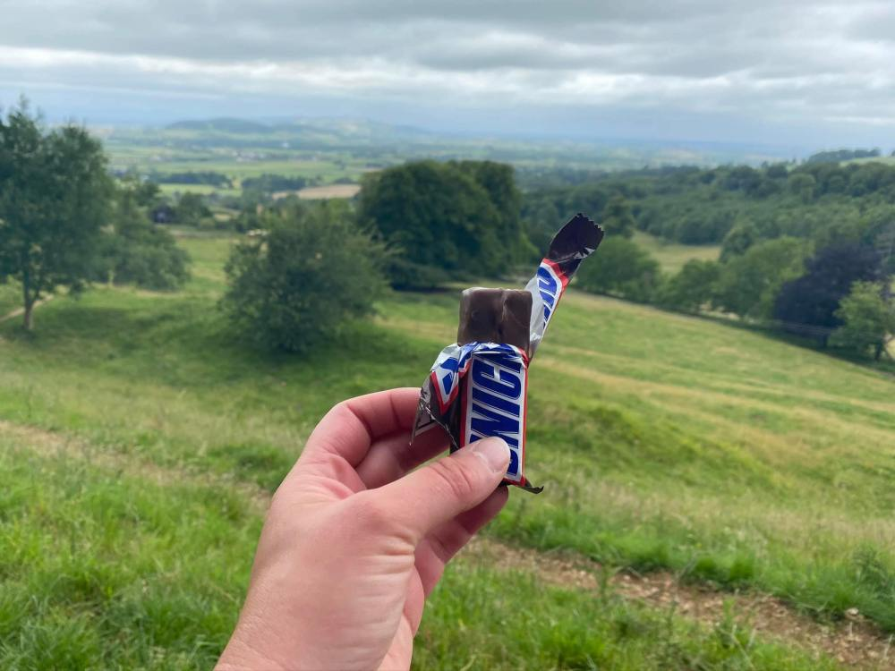 A photo of my hand holding up an unwrapped Snickers bar with the valley in the background.