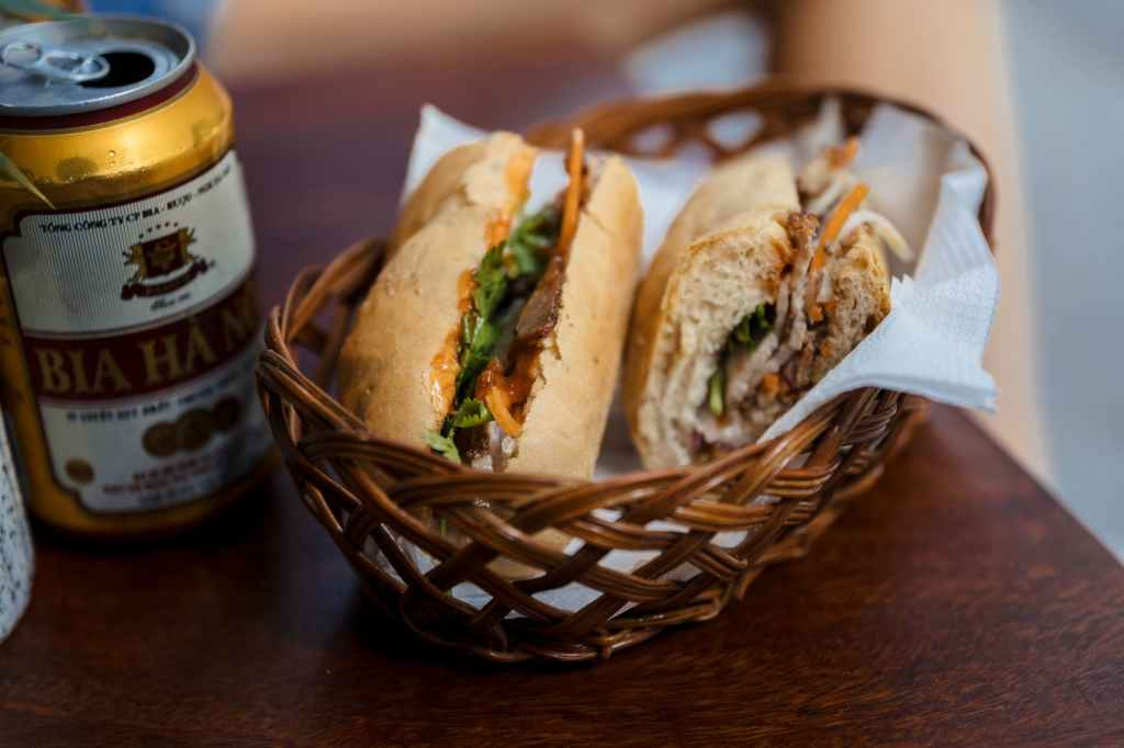 One of the top things to do in Hanoi is to enjoy a Banh Mi, a baguette with pate, meat and veg, as well as a beer.