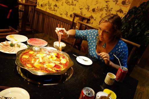 Photo of the hot pot with the meat on the side and me putting some food in it.