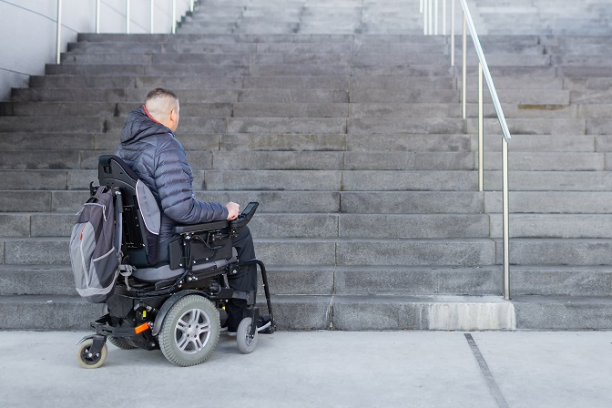 Disabled man with muscular dystrophy on an electric wheelchair who can't get up the stairs.