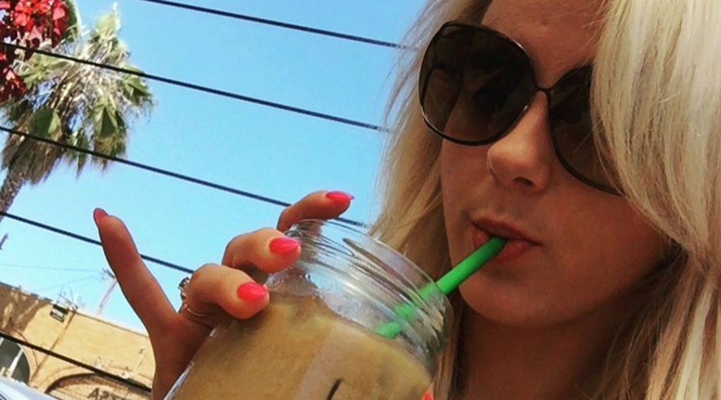 Bree Olson drinking iced coffee from a glass mug