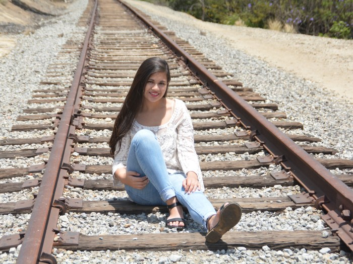Jackie Tester in a white blouse and blue jeans sits on train tracks