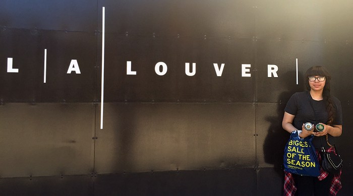 Photo of Jennifer Palacios standing outside the LA Louver Gallery in Venice, California, with 2 cans of Montana Gold spray paint, a shopping bag, and a purse in her hands