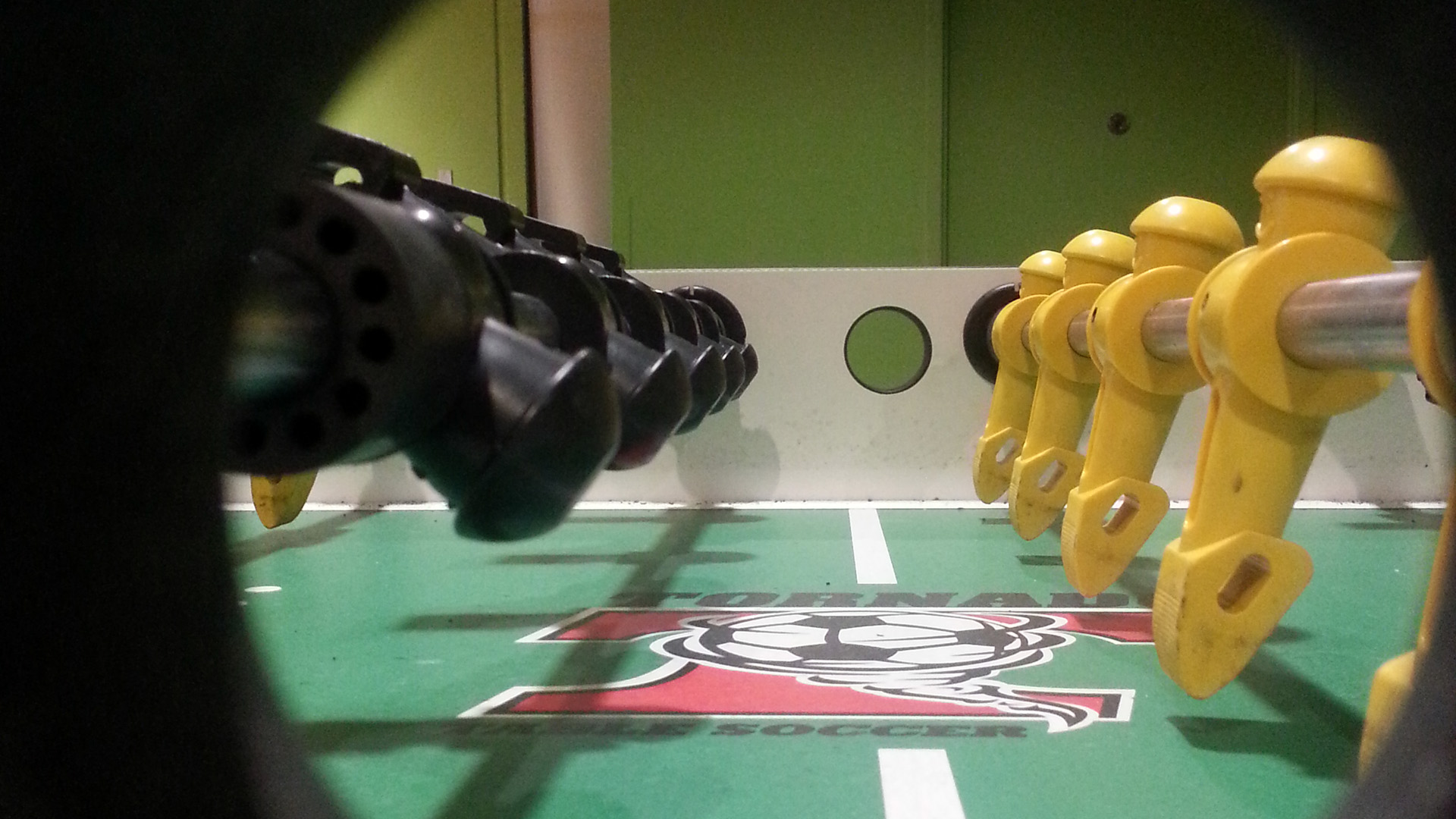 """Photo of a Foosball table with the camera lens in the midfield hole for dropping the ball, so the feeling is of a """"player level view"""" of the field"""
