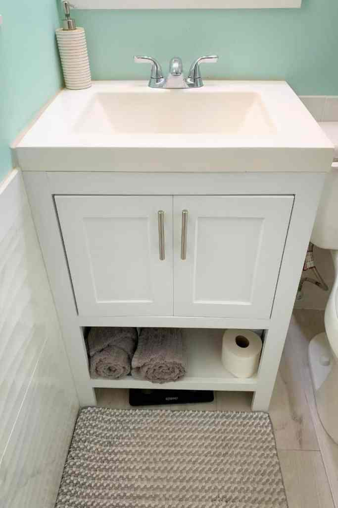 Narrow white vanity with cabinet storage and open storage for a tiny bathroom space