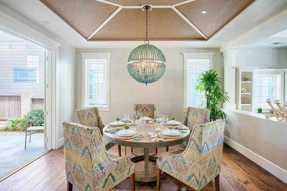 Blue Coastal Dream | Beach House Decor Ideas | Formal dining room with large round chandelier and pattern upholstered seating