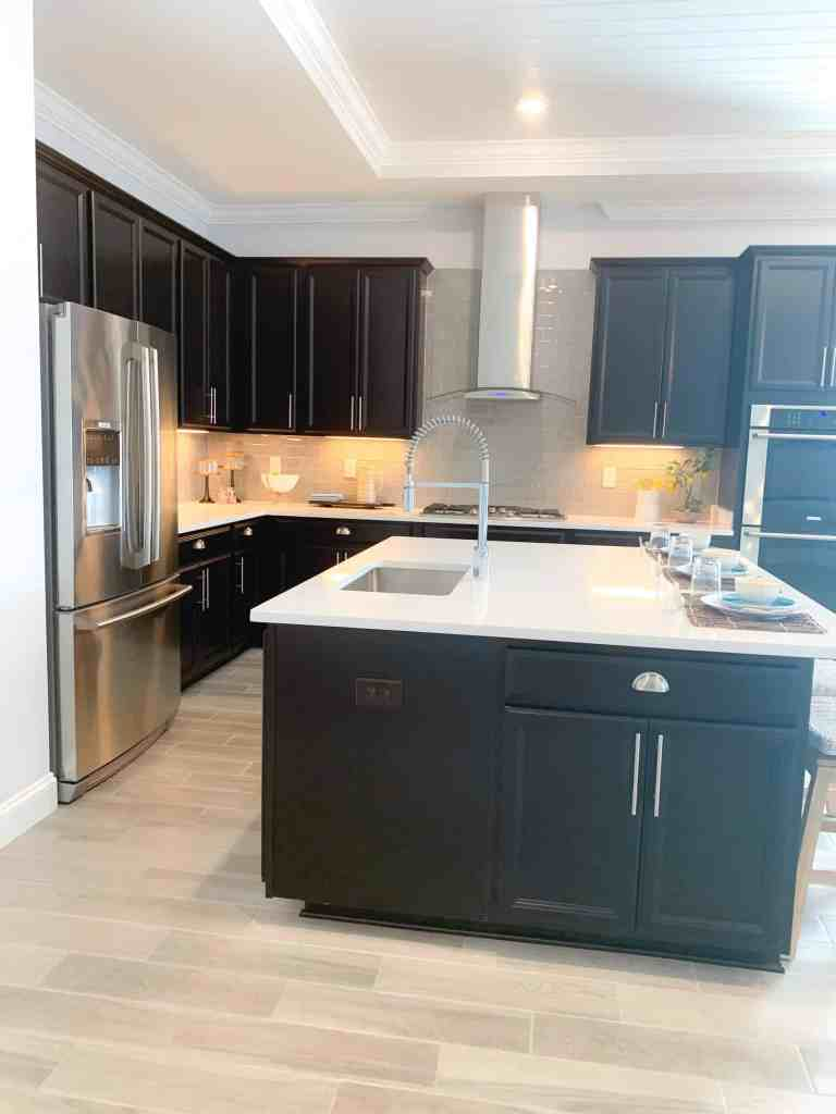 Dark wood cabinets and gray subway tile backsplash in this farmhouse kitchen
