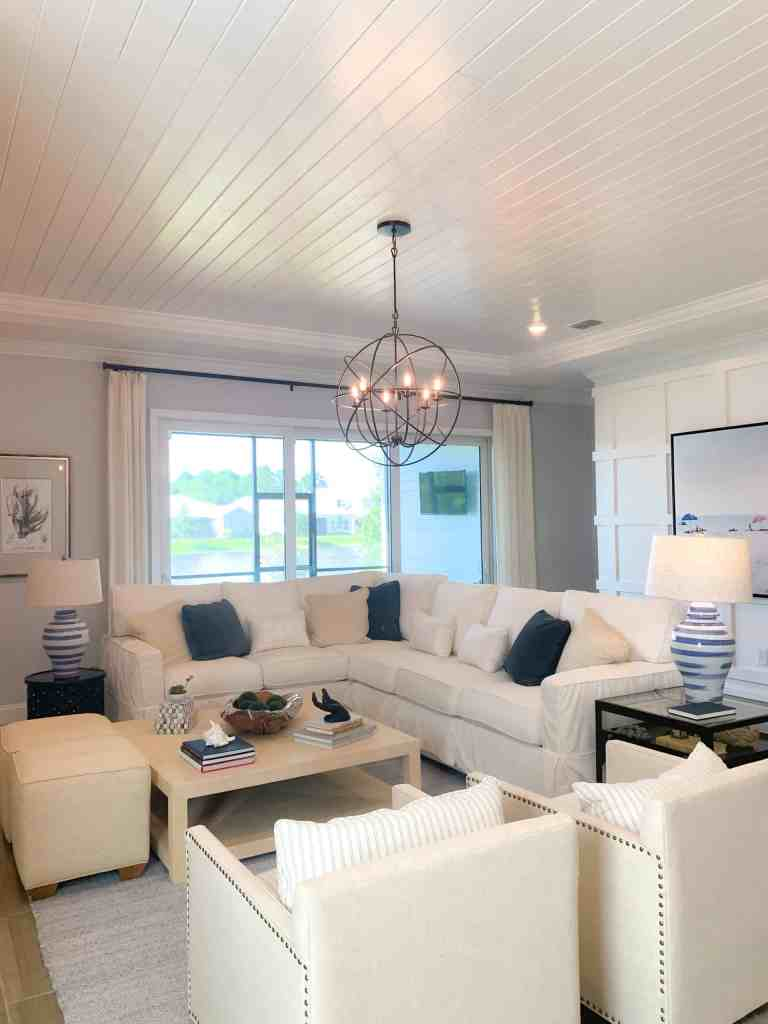 Living room with white couches and navy and beige pillows