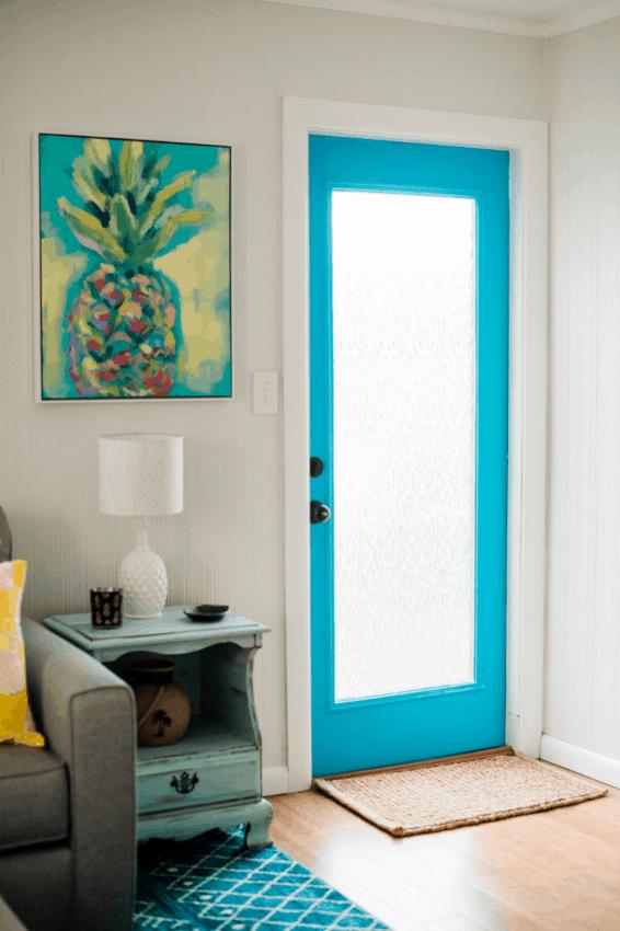 Beach Bungalow Front Door - Pineapple canvas art next to bright blue interior door