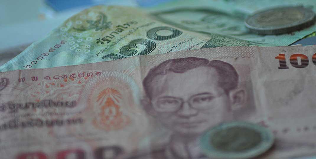 Thai Baht bank notes and coins, 100 baht, 20 bath, and 10 baht coins, THB