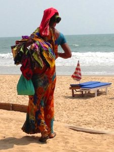 Colorful beach seller in Goa with sarongs under her arm
