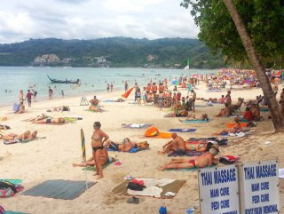 Patong Beach with many sunbathing tourists but no sunbeds or sun umbrellas