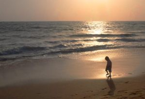 Silhouette of a young boy walking along the beach during sunset.