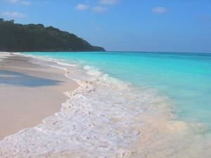 Beautiful shore with white foam spilling in on the beach and turquoise sea water