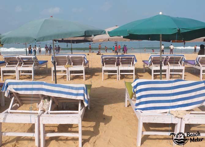 Beach chairs and beach umbrellas facing the sea at Baga Beach, India