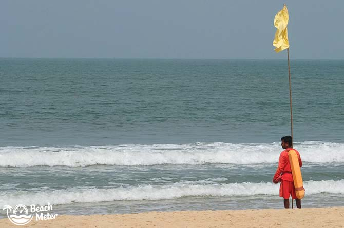 Coast lifeguard putting up a yellow flag signaling safe swimming conditions at one of Goa's beaches