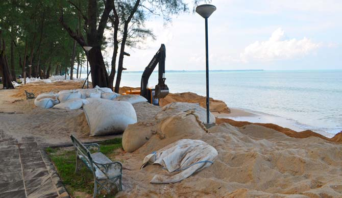 Man-made beaches in Khao Lak Thailand with sandbags and heavy machinery constructing the beach