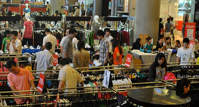 Discount clothing in a Thai shopping mall with customers looking for good bargains.