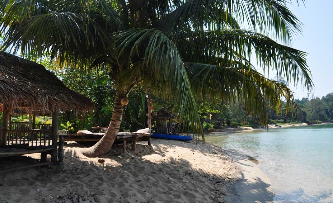Tranquil beach with thatched roofed sala and palm tree. Ao Khao Kwai Beach, koh Phayam เกาะพยาม