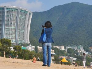 A tourist taking a beach selfie on the beach at Repulse Bay, Hong Kong with a sunbathing girl in the background