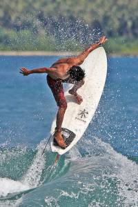 Local Indonesian surfer catapulting his surfboard up in the air as he rides a wave