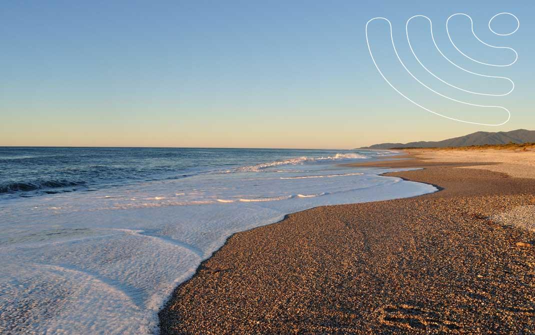 White sea foam spilling onto a beautiful deserted beach and wifi logo