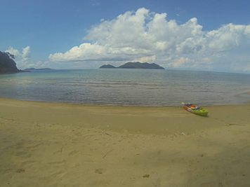 Kayak laying on sandy beach with sea and islands in the background