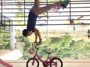 Man doing handstand on children's bike at Upside Down House in Phuket