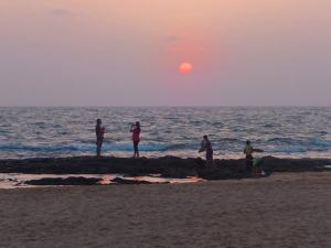 Locals taking pictures and enjoying the sunset at Anjuna Beach in Goa.