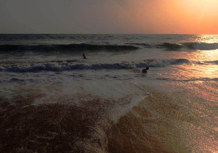 Two men enjoying the rough waters and big waves of Anjuna Beach in Goa at sunset.