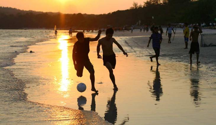 Young men play football (soccer) on the beach on Koh Samet Island in Thailand as the sun sets in the background.