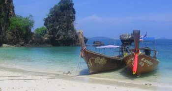 Two longtail boats lying on a beach in Thailand with limestone cliffs in the background