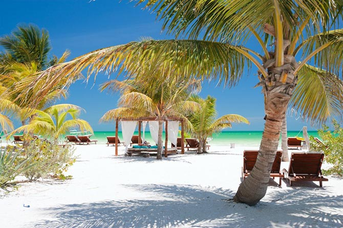 Beach setting with palms and loungers on Holbox Island Beach, Yucatan Peninsula Mexico. One of the world's best serene beaches.