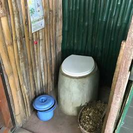 Composting toilet with wood shavings at Escape3Points Ecolodge Ghana