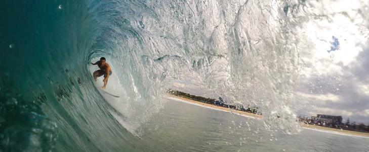 surfer taking a barrel wave in New Zealand