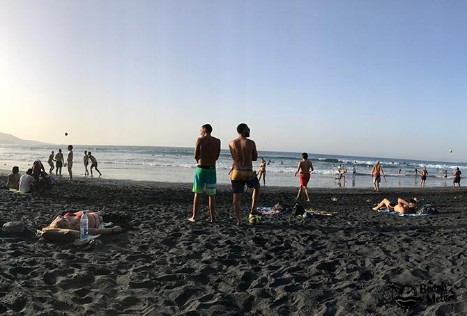 two men taking in the active beach scene on a black sand beach in Spain