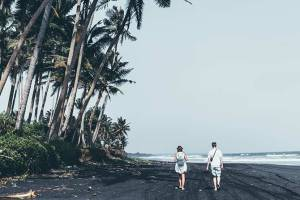 couple walking on black sand tropical beach