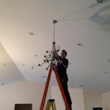 5/8/12 Lenny, the electrician, putting up one of the chandeliers.